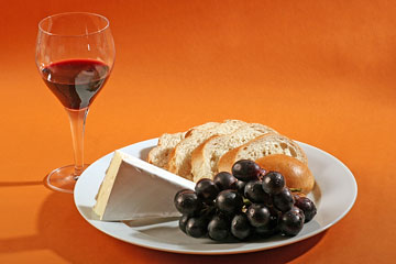 french bread, brie cheese, a bunch of grapes, and a glass of red wine